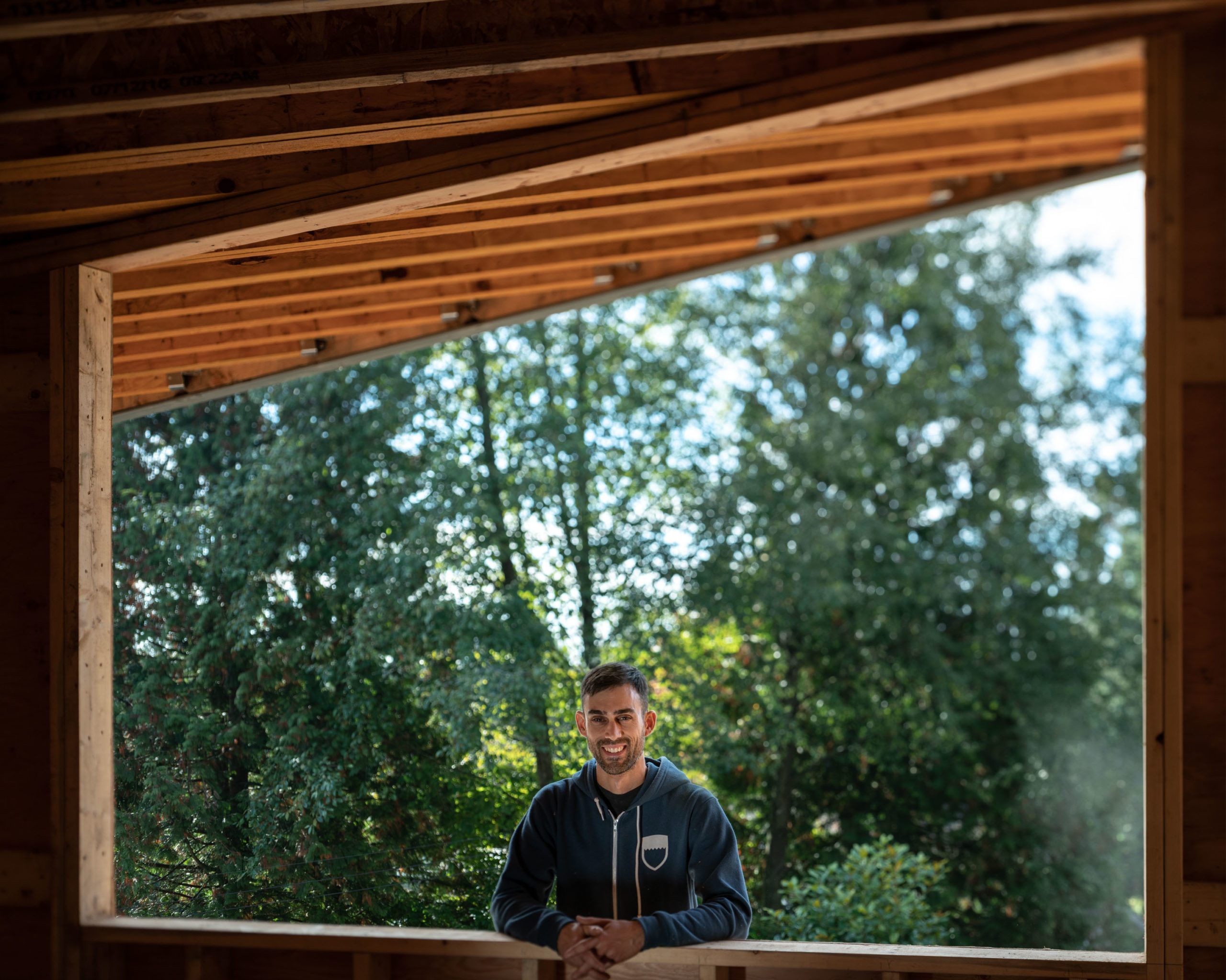 A carpenter stands in a framed-inn picture window with trees behind him.